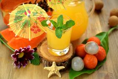 Yellow beverage decorated with mint, straws and little cocktail umbrellas in glass vessels. Surrounded by tropical ts on a wooden table stock photo
