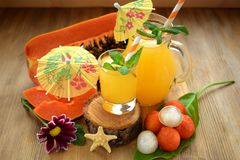 Yellow beverage decorated with straws and little cocktail umbrellas. In glass vessels royalty free stock image