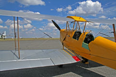 Yellow bi-plane. On the parked on the runway Stock Photography
