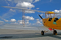 Yellow bi-plane. Parked on the runway Stock Images