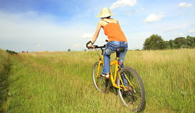 Yellow bicycle. Women ride on yellow bicycle royalty free stock photo