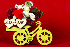 Yellow bicycle with a bucket of flowers & heart, red. Yellow bicycle with a bucket full of flowers in red background Royalty Free Stock Photos