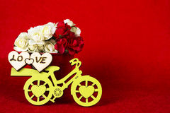 Yellow bicycle with a bucket full of flowers & red. Yellow bicycle with a bucket full of flowers in red background Stock Image