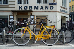 Yellow Bicycle in Copenhagen. An old style bicycle parked by a grocery store in Copenhagen Royalty Free Stock Photo