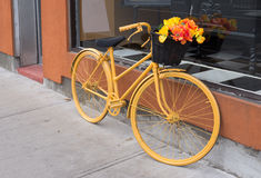 Yellow bicycle with flowers Royalty Free Stock Photo