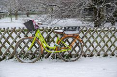 A yellow bicycle is leaning on an brown wood fence in winter Stock Photos