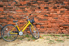 Yellow bicycle and old brick wall. Stock Photo