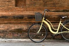Yellow bicycle parking. Near Thai traditional brick wall Royalty Free Stock Photography