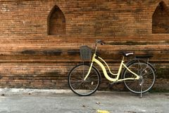 Yellow bicycle parking. Near Thai traditional brick wall Royalty Free Stock Photo