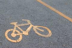Yellow bicycle sign on asphalt bike lane. Royalty Free Stock Image