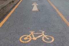 Yellow bicycle sign on asphalt bike lane. Royalty Free Stock Photos
