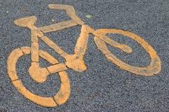 Yellow bicycle sign on asphalt bike lane. Stock Photo