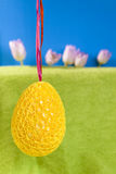 Yellow big Easter egg hanging on purple ribbon on blue and green Stock Photo