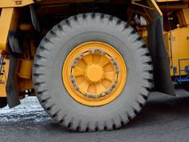 A yellow big wheel, a tow tractor. The image is a large wheel of a truck. It is yellow. It is a wheel of a truck tractor royalty free stock images