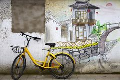 Yellow bike by ancient wall with scenic painting stock image