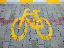 Yellow bike bicycle sign icon on the street. asphalt paint grunge path outdoor floor Stock Images