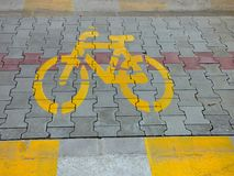Yellow bike bicycle sign icon on the street. asphalt paint grunge path outdoor floor Royalty Free Stock Images