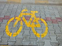Yellow bike bicycle sign icon on the street. asphalt paint grunge path outdoor floor Royalty Free Stock Photos