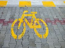 Yellow bike bicycle sign icon on the street. asphalt paint grunge path outdoor floor Stock Photo