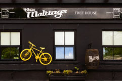 Yellow bike on outside wall of The Maltings Free House, York Stock Photography