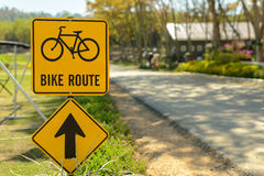 A yellow bike route sign on the side of the road. Stock Photography