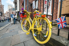 Yellow bike in York, UK. York, United Kingdom - July 5, 2014: People walk past a decorated yellow bike in York city center during the Tour de France race. Tour royalty free stock photography
