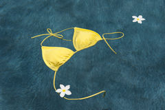 Yellow bikini floating with flowers Royalty Free Stock Image