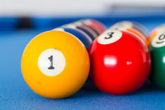 Yellow billiard ball number one and other colorful balls placed Stock Photography