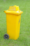 A yellow bin in the park Royalty Free Stock Photo