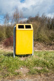Yellow bin at a side of the road Stock Images