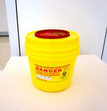 Yellow biohazard medical container. Yellow biohazard medical contaminated sharps clinical waste container  on the table Stock Image