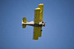 Yellow biplane. Crop duster, flying against the blue sky Royalty Free Stock Photos