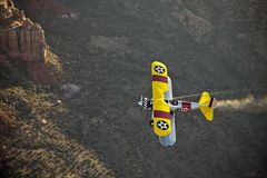 Yellow biplane over desert Stock Photo