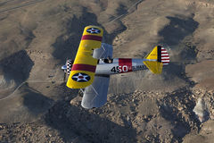 Yellow biplane over desert Royalty Free Stock Photos