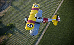 Yellow biplane over field Royalty Free Stock Image