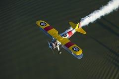 Yellow biplane over lake Stock Image