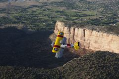 Yellow biplane over large canyon Stock Photo