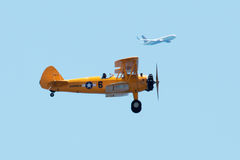 Yellow biplane performs at airshow with commercial flight in vie royalty free stock photos