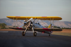 Yellow biplane sitting on runway Stock Image
