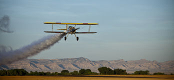 Yellow biplane with smoke. Royalty Free Stock Images