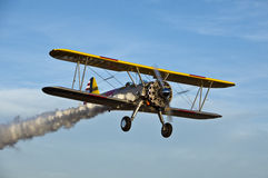 Yellow biplane with smoke. Stock Photo