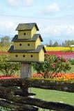 Yellow birdhouse in garden Stock Photography
