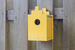 Yellow birdhouse on a wooden fence Stock Images
