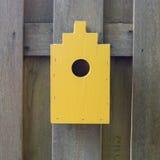 Yellow birdhouse on a wooden fence Stock Photos