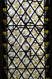 Yellow Birds Stained Glass Window. Decorative, elegant yellow and white birds and flowers vertical stained glass window royalty free stock image