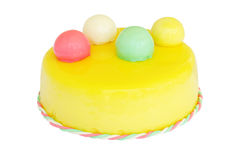Yellow birthday cake with colored balls isolated on white stock image