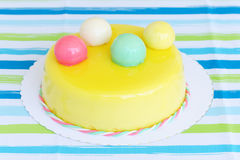 Yellow birthday cake with colored balls royalty free stock photo