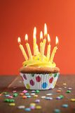 Yellow birthday cupcake full of candles Stock Photography
