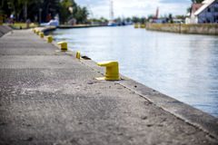 Yellow bitt on port channel quayside mooring. Many yellow bitt on port channel quayside mooring Royalty Free Stock Images
