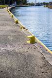 Yellow bitt on port channel quayside mooring. Many yellow bitt on port channel quayside mooring Stock Photo